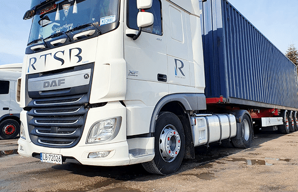 white parked RTSB container truck carrying a blue container.